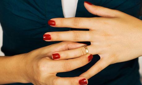 Woman removing wedding ring (Mockridge Investigations)